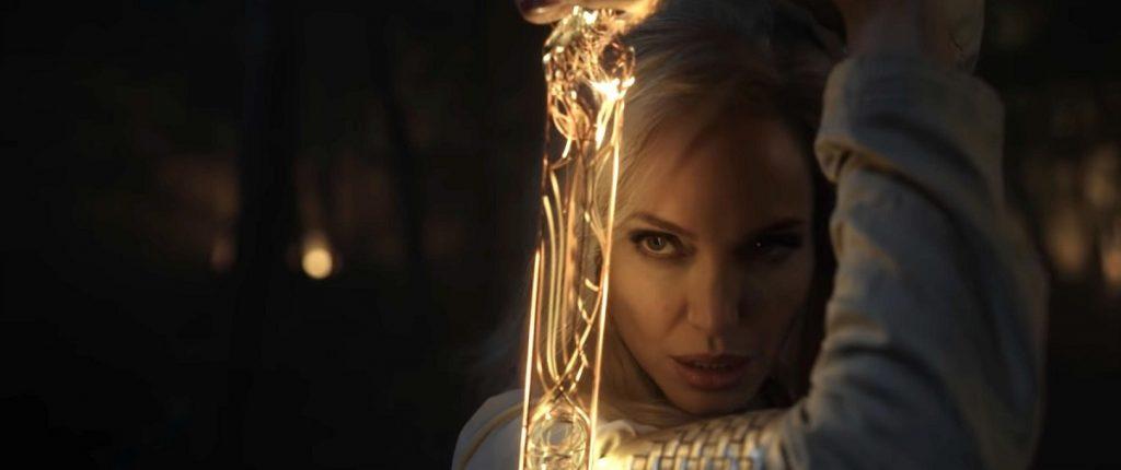Portret cu Angelina Jolie în rolul zeiței Thena în noul film Marvel, Eternals în timp ce ține în mână o sabie făurită din energia cosmică