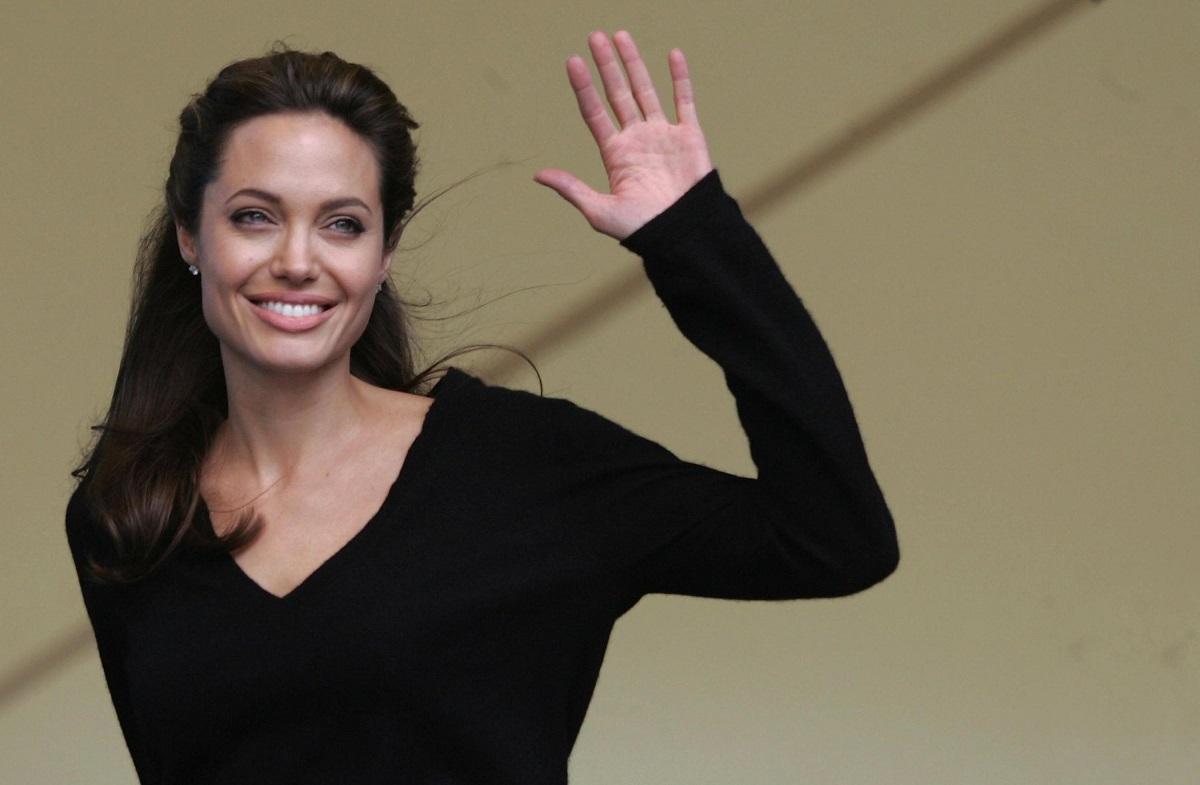 Angelina Jolie îmbrăcată într-o bluză neagră, zâmbind în timp ce face cu mâna stângă publicului în timpul conferinței live pe care a susținut-o cu muzicianul Peter Gabriel despre Africa de Sud în data e 2 iulie 2005