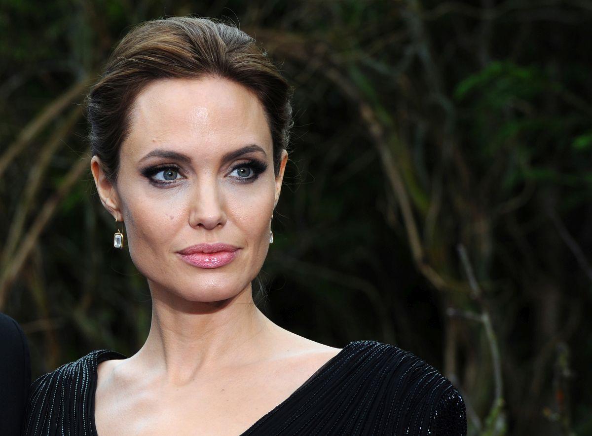 Agelina Jolie , îmbrăcată în negru, cu părul prins și cercei lungi, participă la un eveniment privat la Palatul Kensigton, în 2014