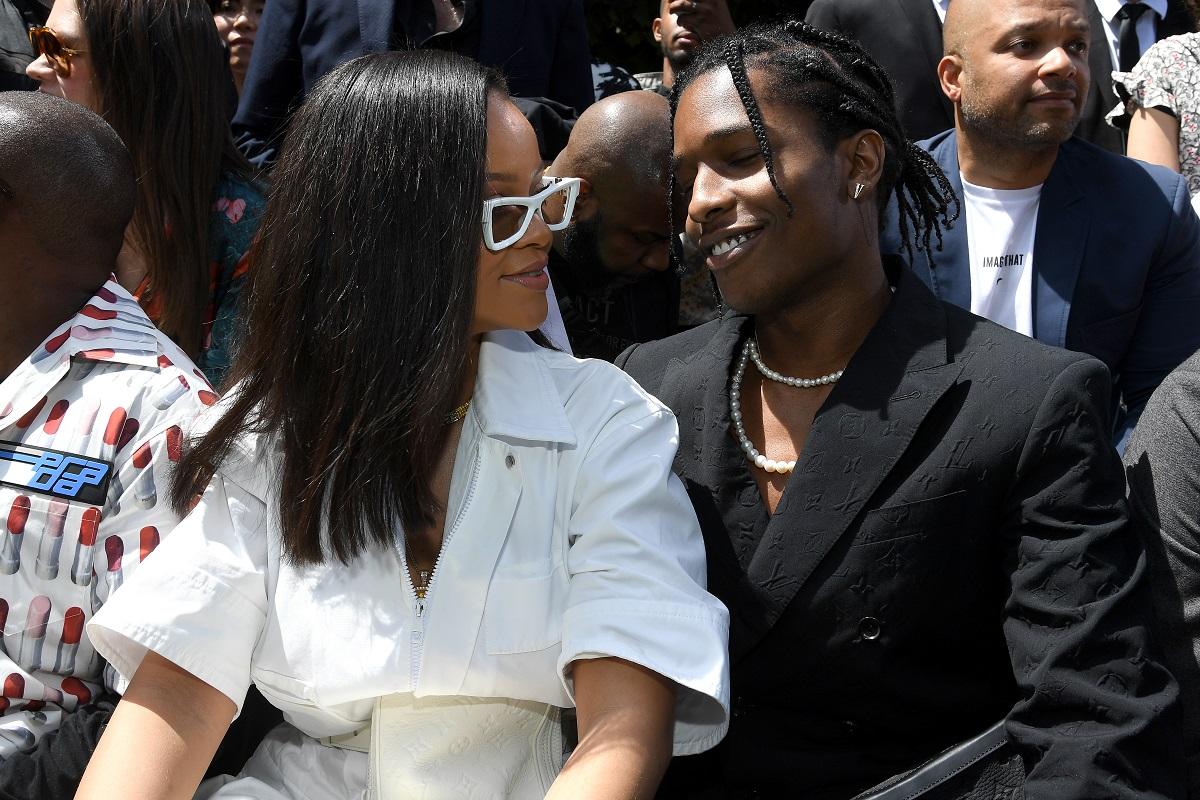 Rihanna îmbrăcată într-o ținută albă în timp ce îl privește pe rapper-ul Asap Rocky la Paris Fashion Week în anul 2018