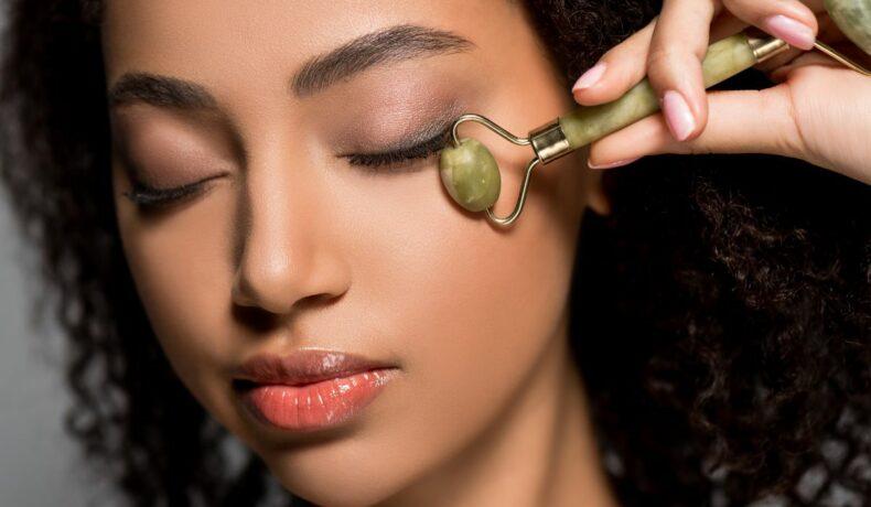 O femeie, cu ochii închiși, își masează fața cu o rolă de jad