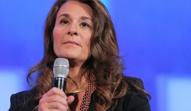 Melinda Gates, ține un microfon în mână și îmbrăcată într-o bluză cu imprimeu polka dor, peste care are un sacou negru