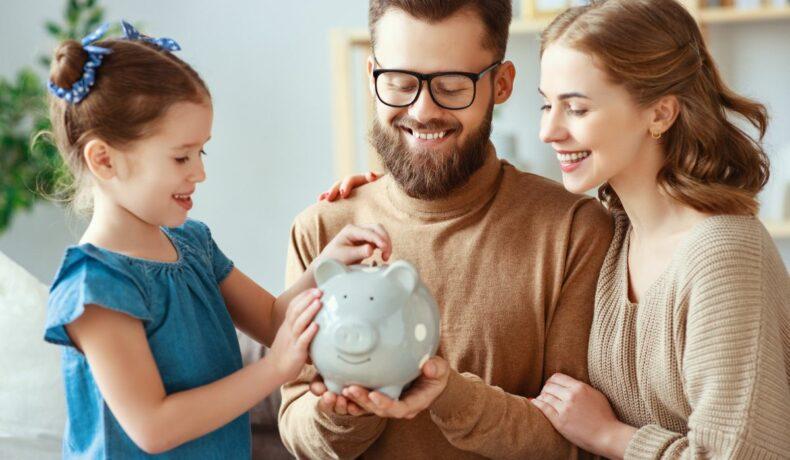 O famiie formată din mama, tata și fetița, stau în jurul unei pușculițe albe de bani
