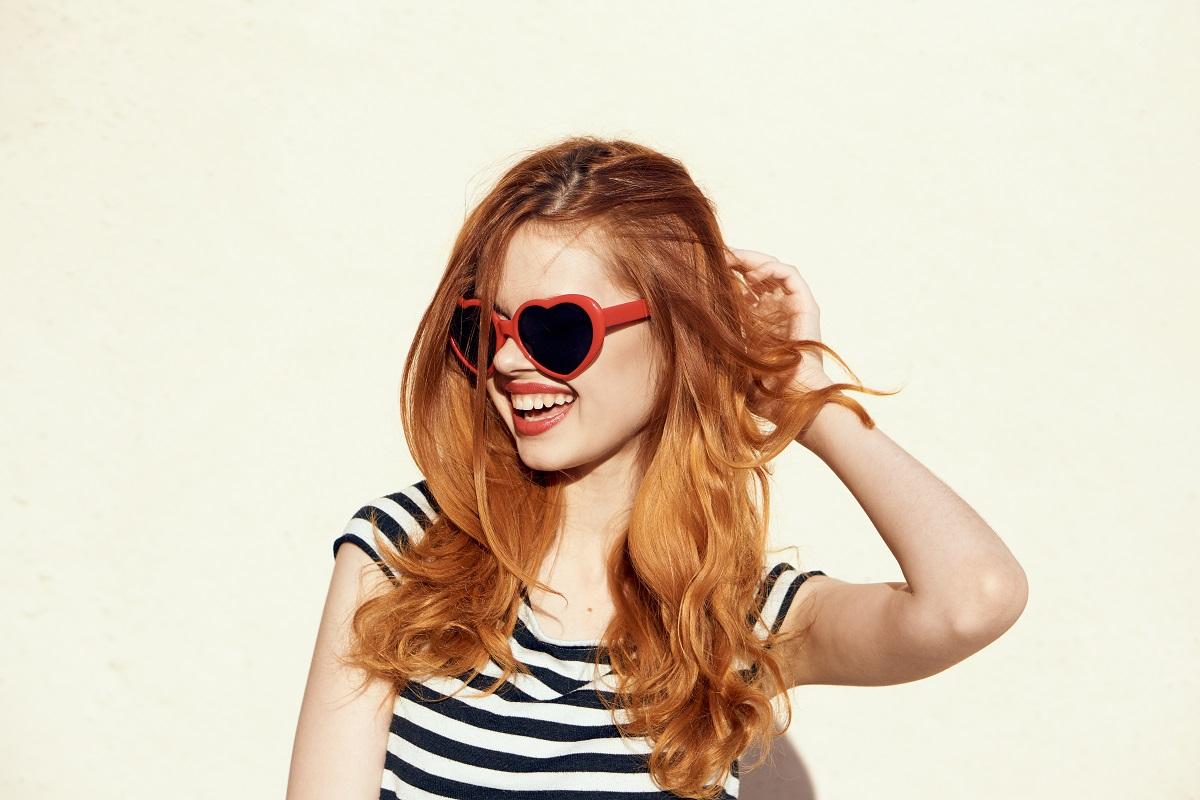 Femeie cu părul roșcat care poartă un tricou în dungi alb-negru și o pereche de ochelari roz în timp ce zâmbește la ce culori de păr ar trebui să aleagă