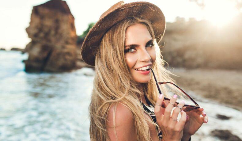 O tănără, cu părul blond și pălărie de soare, ce are în spate marea și niște stânci