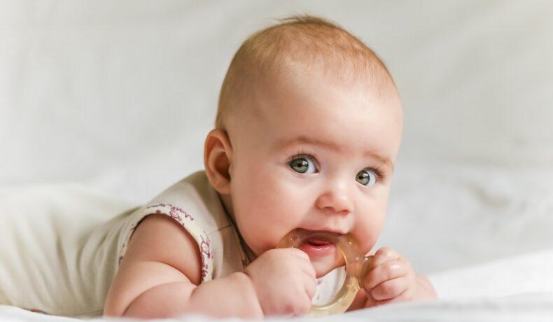 Un bebeluș cu ochișorii albaștri care ține în mână un inel de cauciuc pe care îl roade, îmbrăcată într-un body alb în timp ce stă pe așternuturi albe așteptând să primească unul dintre cele mai populare nume-de-copii-în-anul-2021
