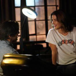 Actrișa Cobie Smulders în rolul lui Dex Parios îmbrăcată într-un tricou alb în timp ce stă aplecată peste un birou în timp ce privește un bărbat într-o scenă din sezonul 1 al serialului Stumptown
