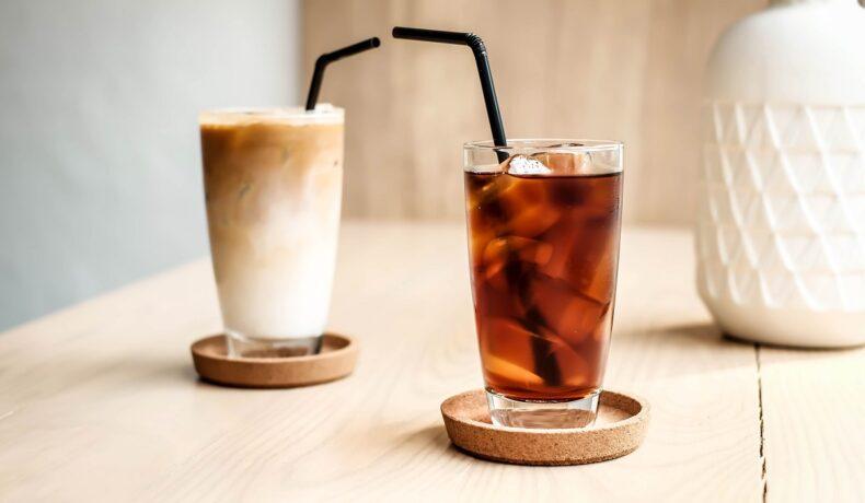 două pahare cu pai negru așezate pe un blat de lemn care ilustrează Cold Brew vs Iced Coffee și felul cum se prepară și care este diferența dintre ele