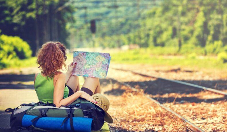 O fată, așezată pe rucsac, așteaptă trenul, într-o gară