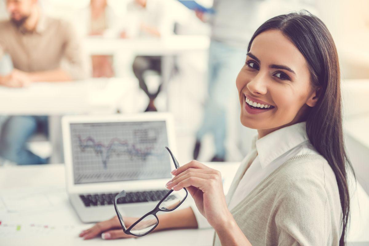 O femeie tânără, lucrează la birou, în fața calculatorului, se întoarce zâmbind, cu ochearii în mână