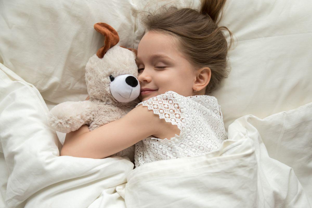 O fetiță, zâmbește, în timpul somnului, în vreme ce își strânge în brațe ursulețul
