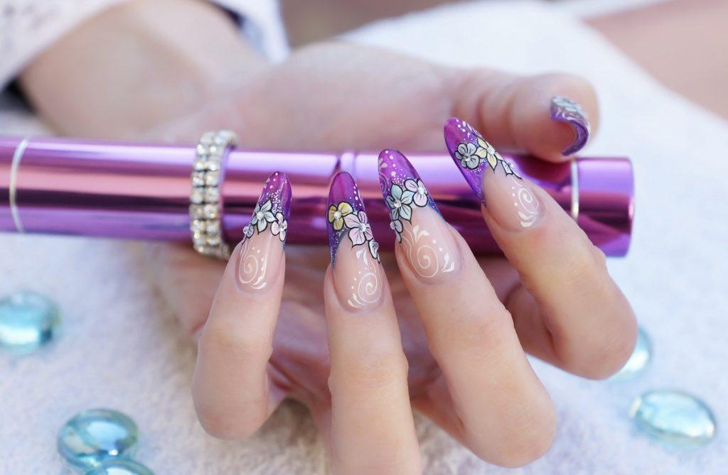 manichiură în formă de balerină colorate în nude și cu modele florale mov care țin în mână un toc violet care să te ajute cum să alegi forma ideală pentru unghii