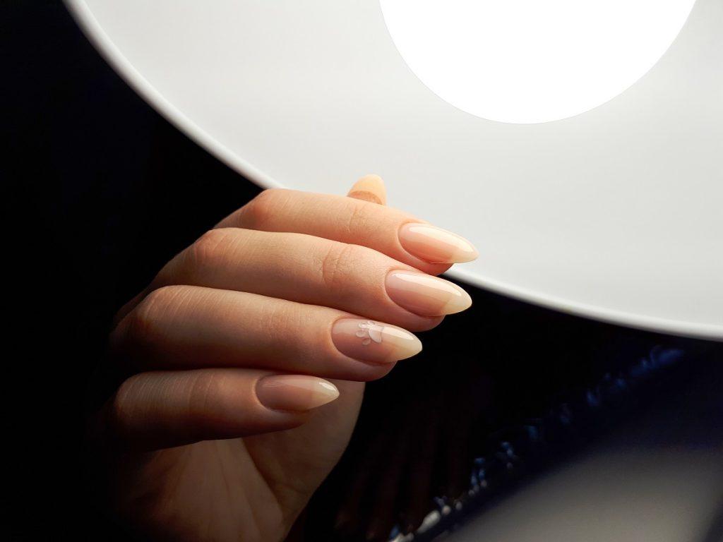 manichiură în formă de migdală care stau sub o lampă aprinsă care să te ajute să alegi forma ideală pentru unghii
