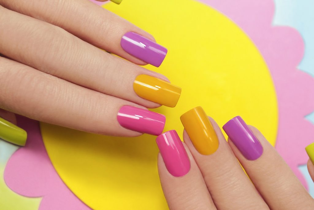 manichiură în fromă pătrată colorată în galben, roz și mov care stau pe o floare galbenă
