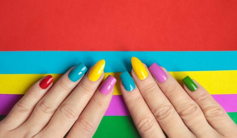 două mâini pe un fundal colorat cu unghiile făcute în nuanțe de roșu, albastru, galben, violet și verde care ilustrează cum să îți alegi forma ideală pentru unghii