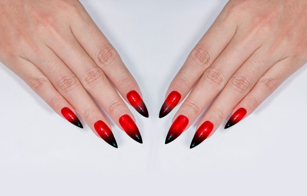 manichiură în fromă stiletto și de culoare roșu cu negru care stau pe o masă albă care să te ajute cum să alegi forma ideală pentru unghii