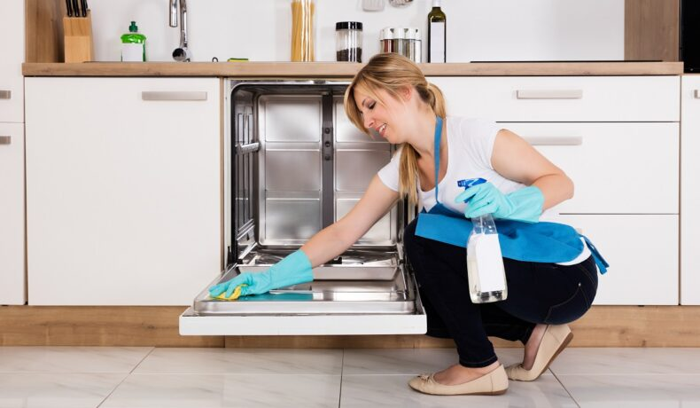 Femeie blondă îmbrăcată cu pantaloni negri, tricou alb, șorț și mănuși albastre care ține în mână o soluție specială pentru a arăta cum să cureți corect o mașină de spălat vase