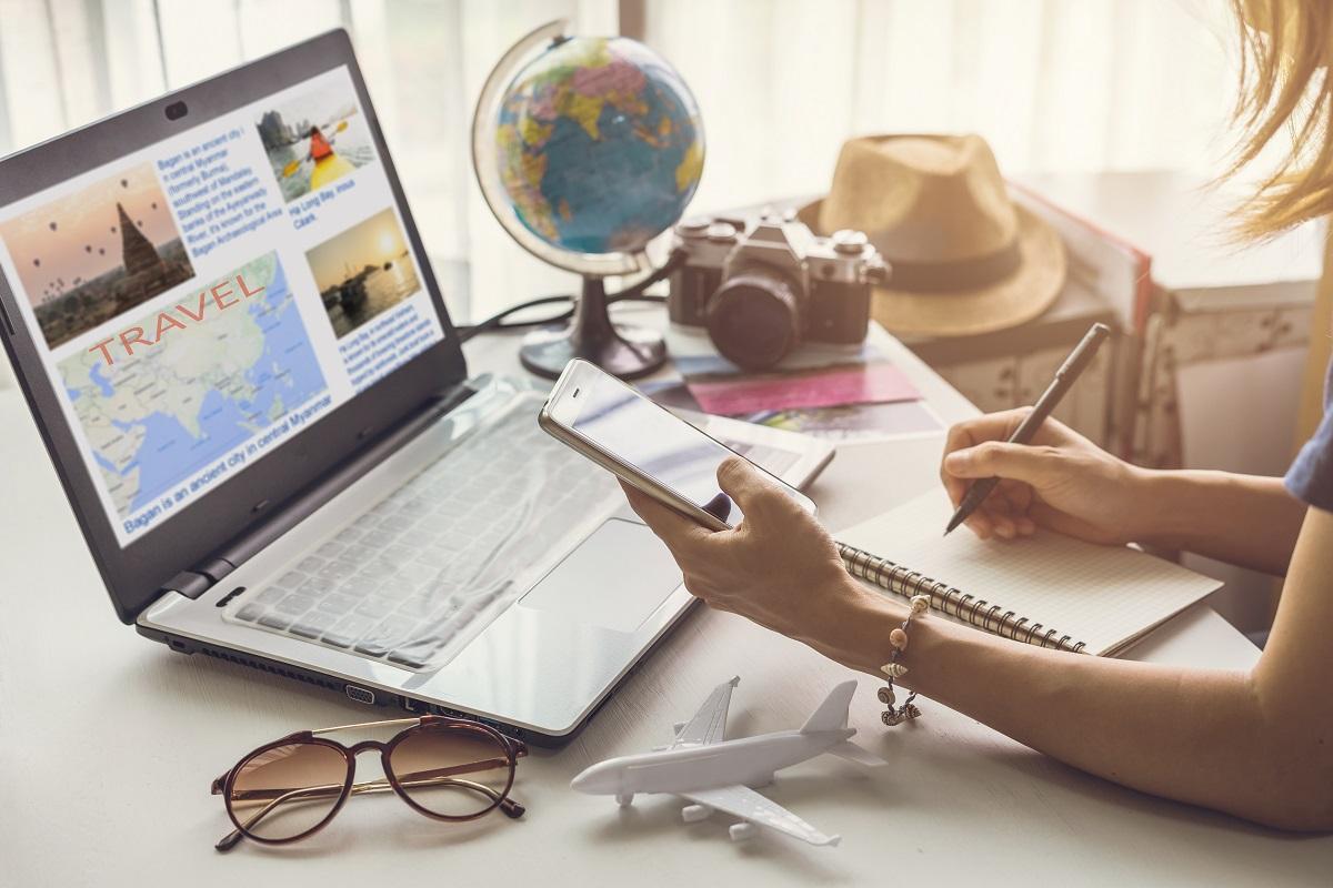 o mână care ține un telefon în timp ce notează oe o foaie aflată pe un birou pe care este așezat un laptop, o pereche de ochelari, un aparat de fotografiat, un glob pământesc și o pălărie în timp ce își planifică vacanța de vis