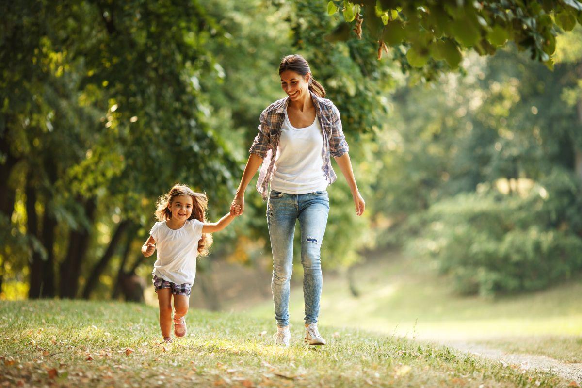 Mama și fiica, ținându-se de mână și jucându-se în parc