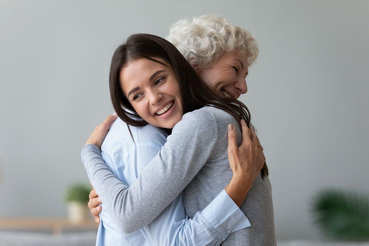 O femei tănără, îmbrățișează o alta în vârstă. Ambele zâmbesc și au capetele întoarse într-o parte