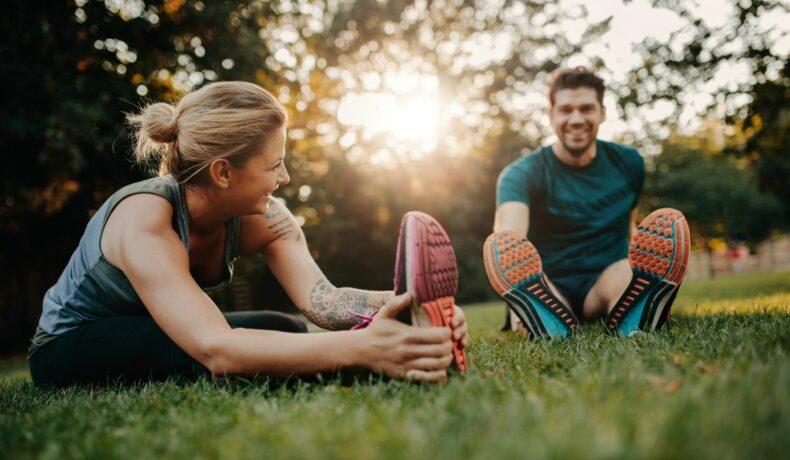 Un cuplu care face stretching pe iarbă