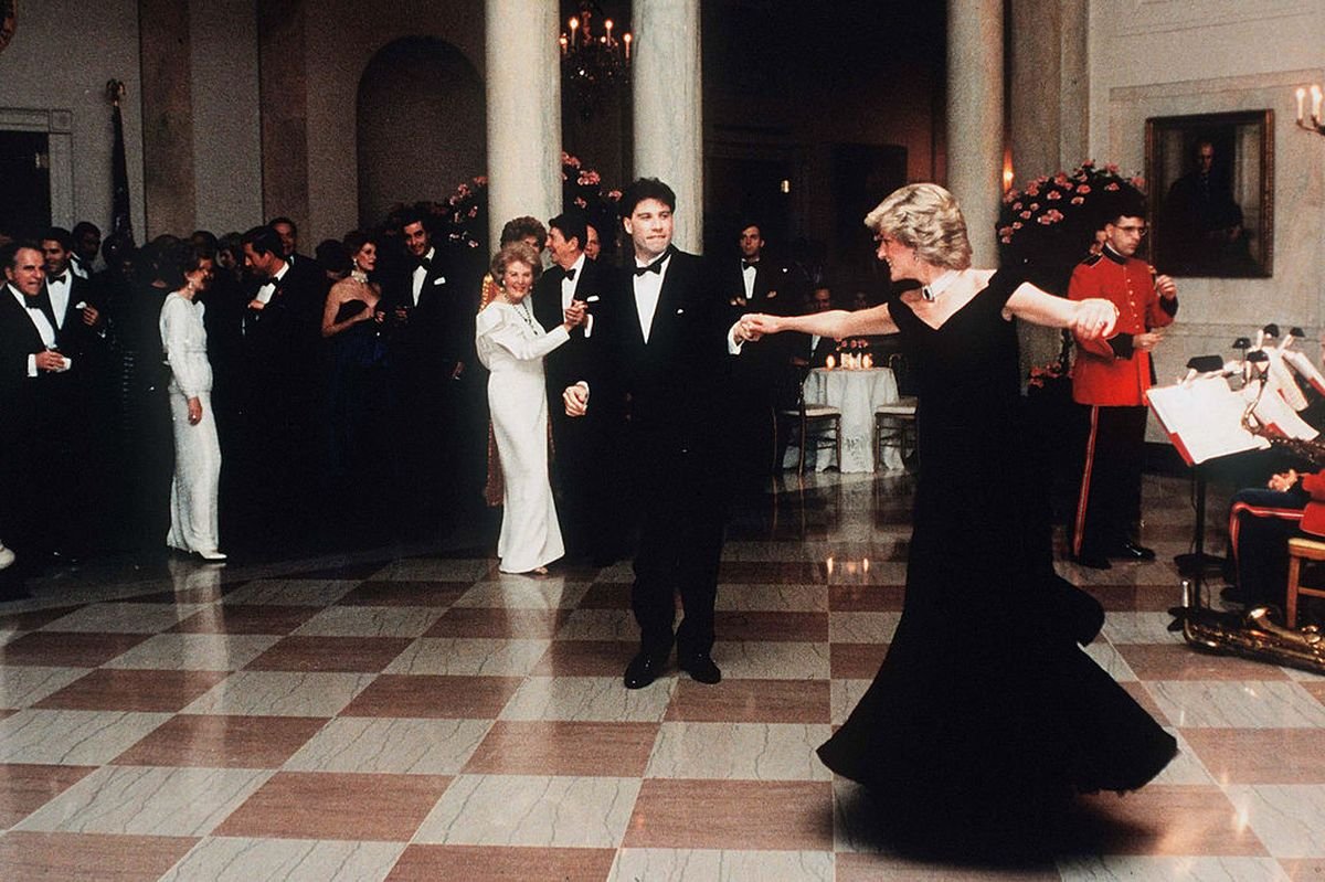 John Travolta, îmbrăcat în costum negru, dansează cu Prințesa Diana, ce poartă o rochie de gală, de culoare neagră