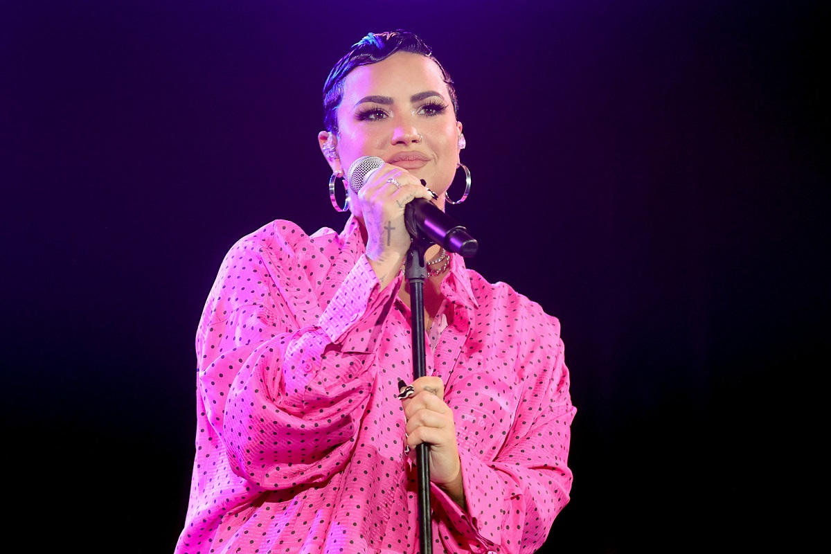 Demi Lovato pe scenă în fața microfonului îmbrăcată într-o rochie roz la premiera evenimentului documentarului său Dancing with the devil în martie 2021
