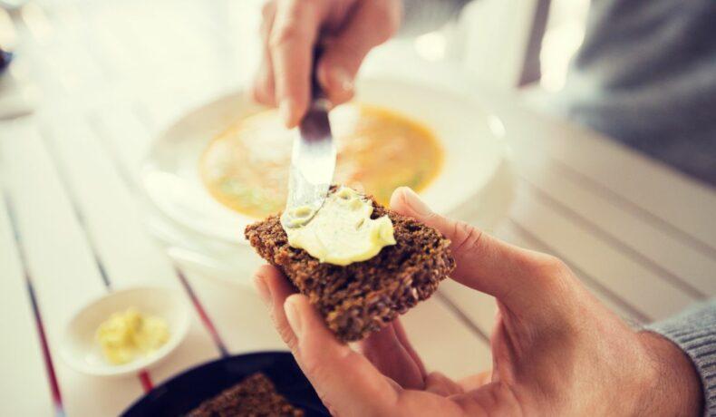 O pereche de mâini ce țin în mână o bucată de pâine pe care este întins unt cu cuțitul