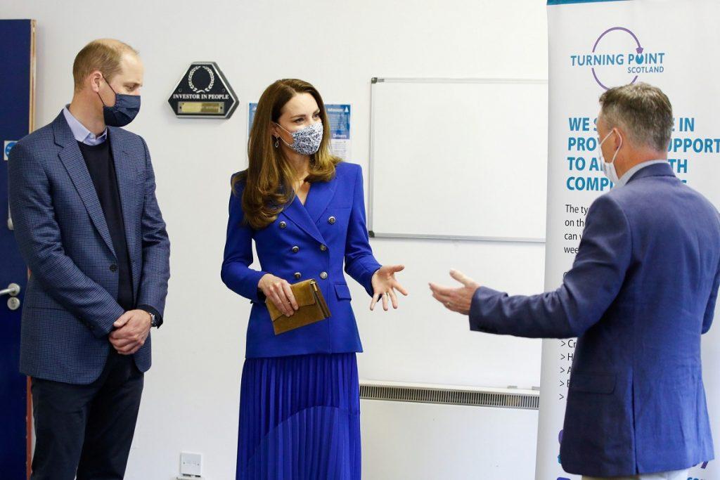 Kate Middleton îmbrăcată într-o ținută monocromă albastră alături de soțul ei Prințul william în timp ce discută cu Neil Richardson la o întâlnire oficială din Scoția