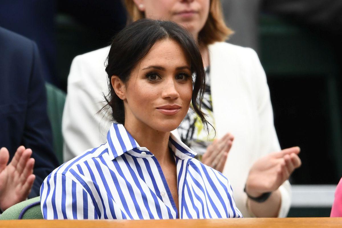 Ducesa de Sussex, îmbrăcată într-o cămașă albastră cu dungi albe, și părul prins