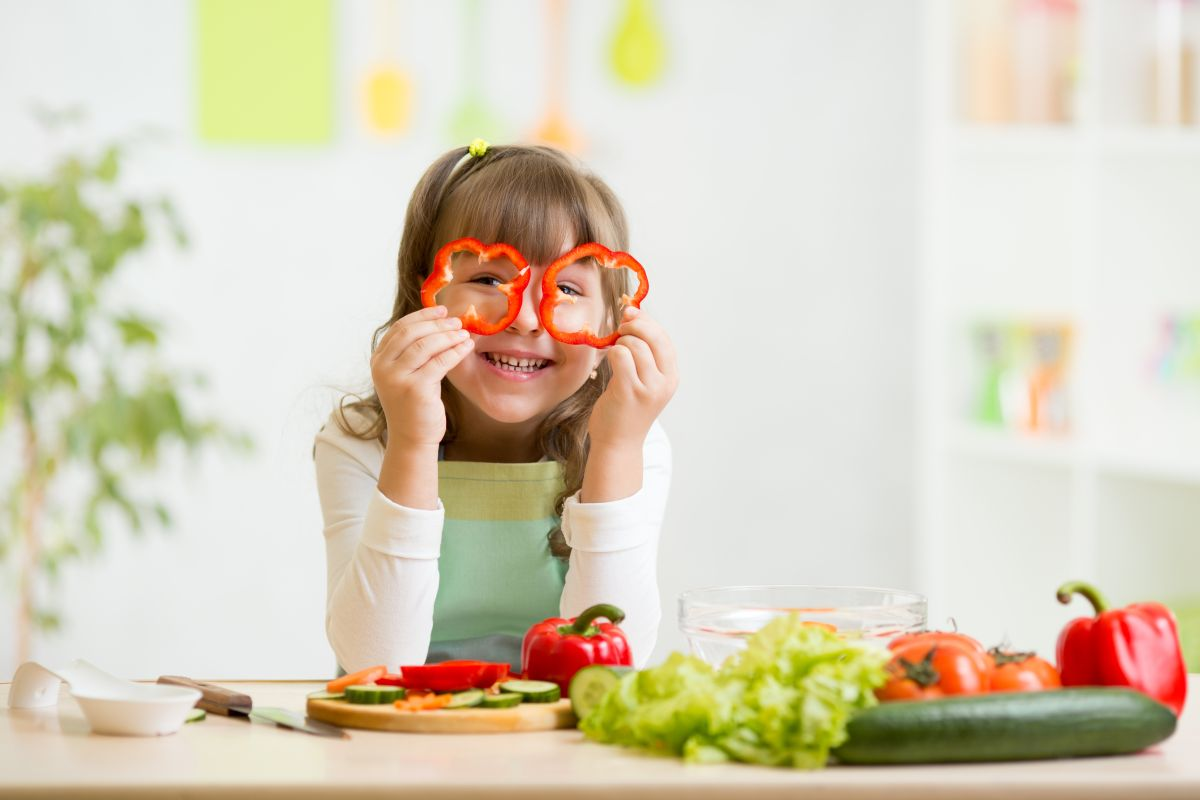 O fetiță care zâmbește, își pune două rondele de ardei pe post de ochelari