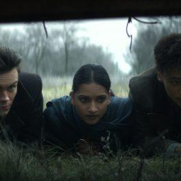 Personajele Kaz Brekker, Inej Ghafa și Malyen Orestev interpretate de actorii Freddy Carter, Amita Suman și Archie Renaux în timp ce stau întinși pe iarbă într-o scenă din Shadow adn Bone care ilustrează spionajul unei case în care trebuie să pătrundă