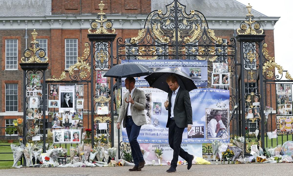 Prințul William alături de Prințul Harry în timp ce țin două umbrele și trec prin fața porții Castelului Kensington în 2017 înainte să afle adevărul despre interviul Prințesei Diana