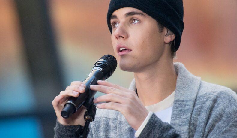 Justin Bieber pe scenă în New York 2015 cântând la NBC's Today în timp ce ține în mână microfonul și poartă o căciulă neagră înainte de a renunța la dreaduri