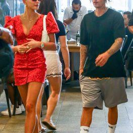 Justin Bieber îmbrăcat într-un tricou negru, cioraăi lungi albi, ochelari roz și o pereche de pantaloni scurți gri, alături de soția lui care este îmbrăcată într-o rochie scurtă rosie