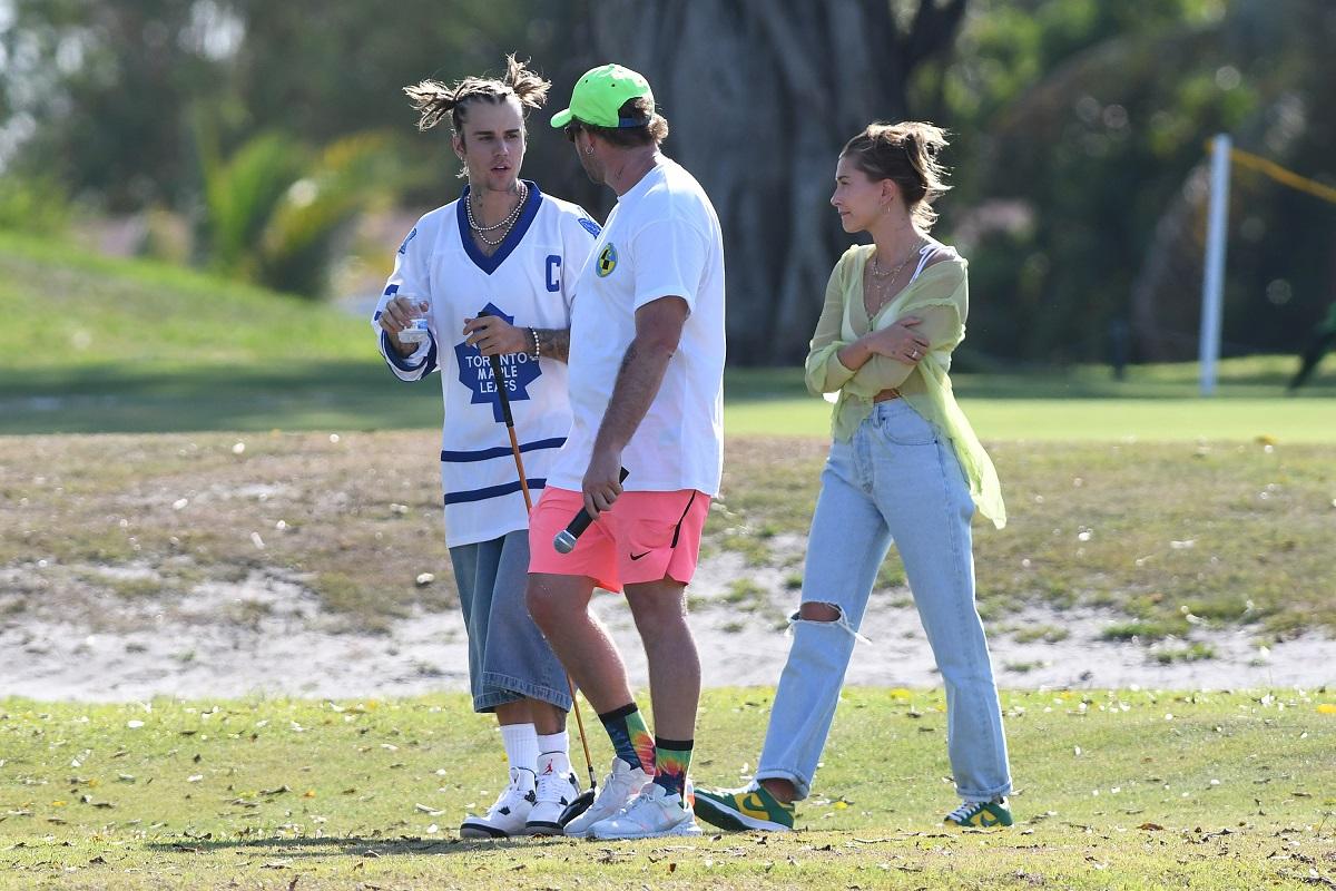 Justin Bieber îmbrăcat în pantaloni scurți și un tricou alb alături de prietenul său rapper care poartă o pereche de pantaloni roz, un tricou alb și o șapcă verde și soția lui Bieber care poartă o pereche de blugi și o cămașă crem