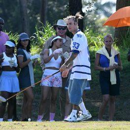 Justin Bieber îmbrăcat în pantaloni scurți albaștrii și un tricou alb larg în timp ce joacă golf alături de prietenii care îl susțin din spatele său