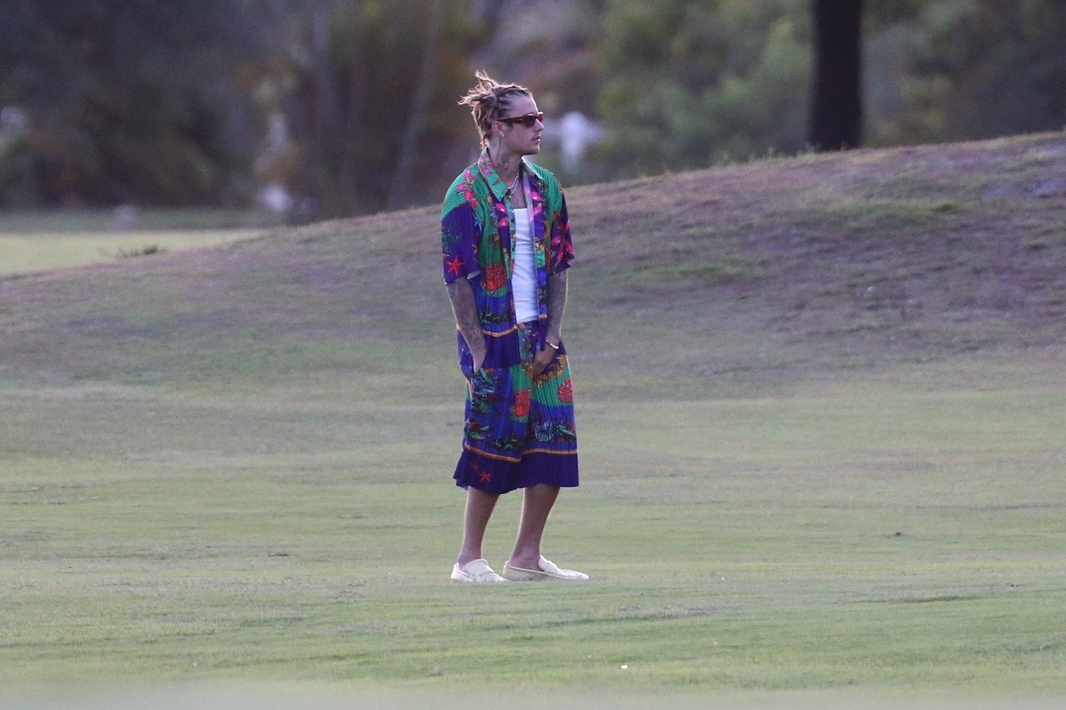 Justin Bieber pe o pajiște verde îmbrăcat într-un tricou alb și o cămașă albastră cu modele florale