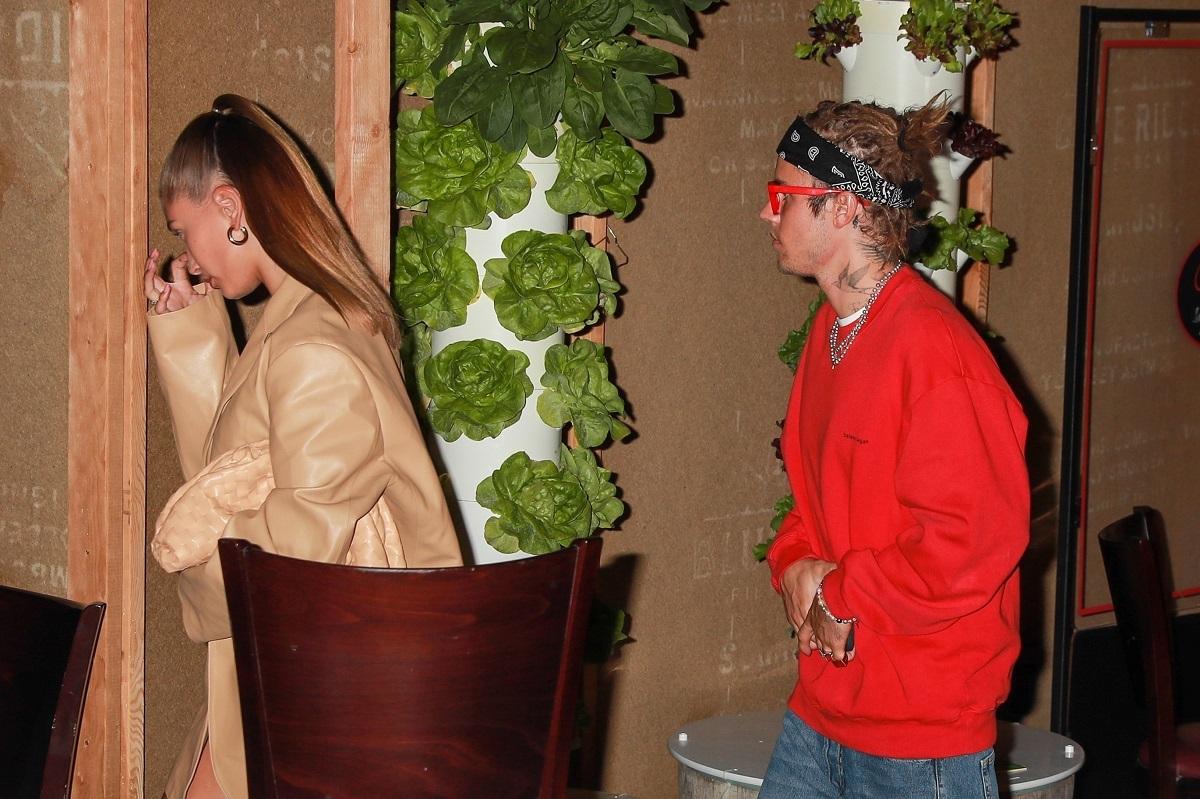 Justin Bieber într-o bluză roșie și ochelari roz în timp ce o urmează pe soția sa care este îmbrăcată într-o rochie crem largă