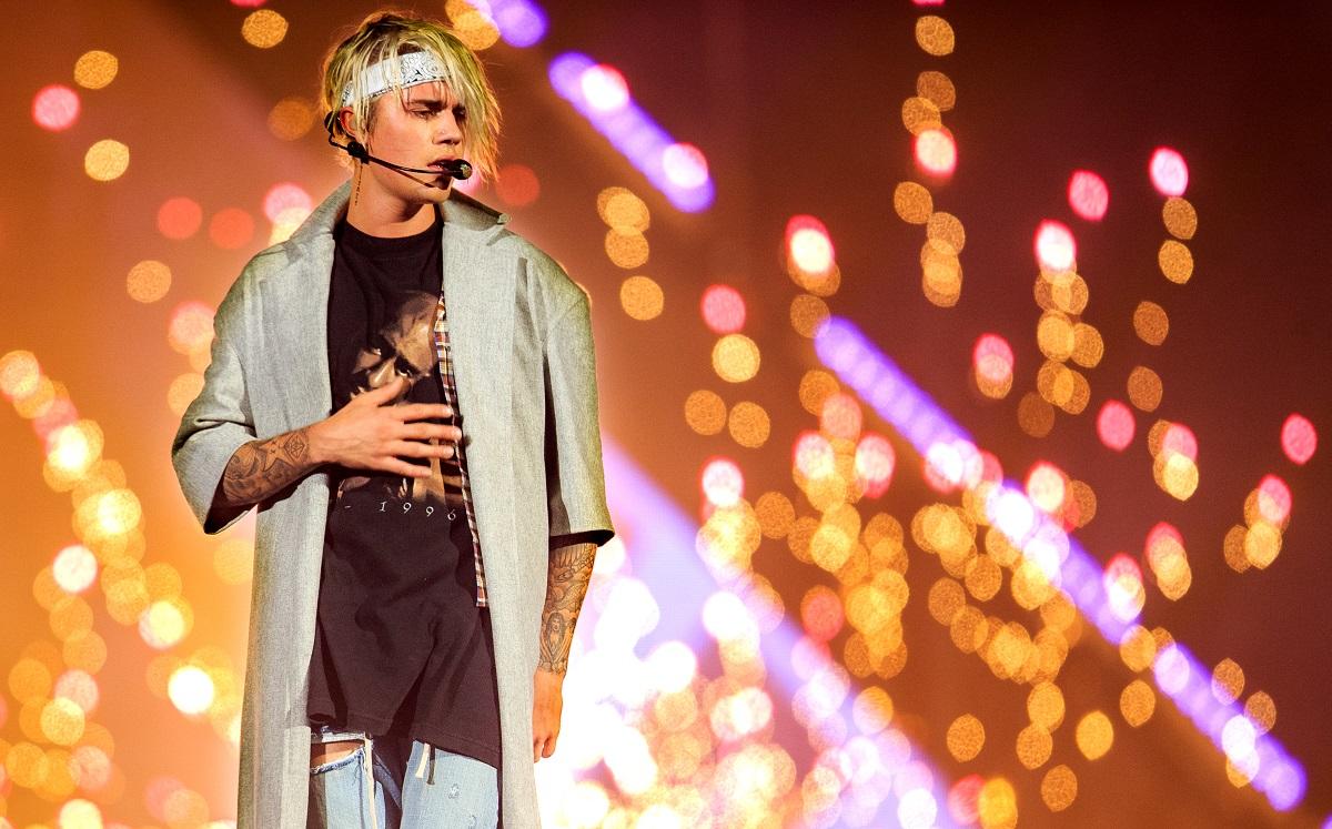 Justin Bieber s-a lăsat pe mâinile stiliștilor și este îmbrăcat într-un tricou negru și o cămașă gri desfăcută, cu părul prins într-o bandană albă în timp ce în spatele său apare publicul plin de lumini