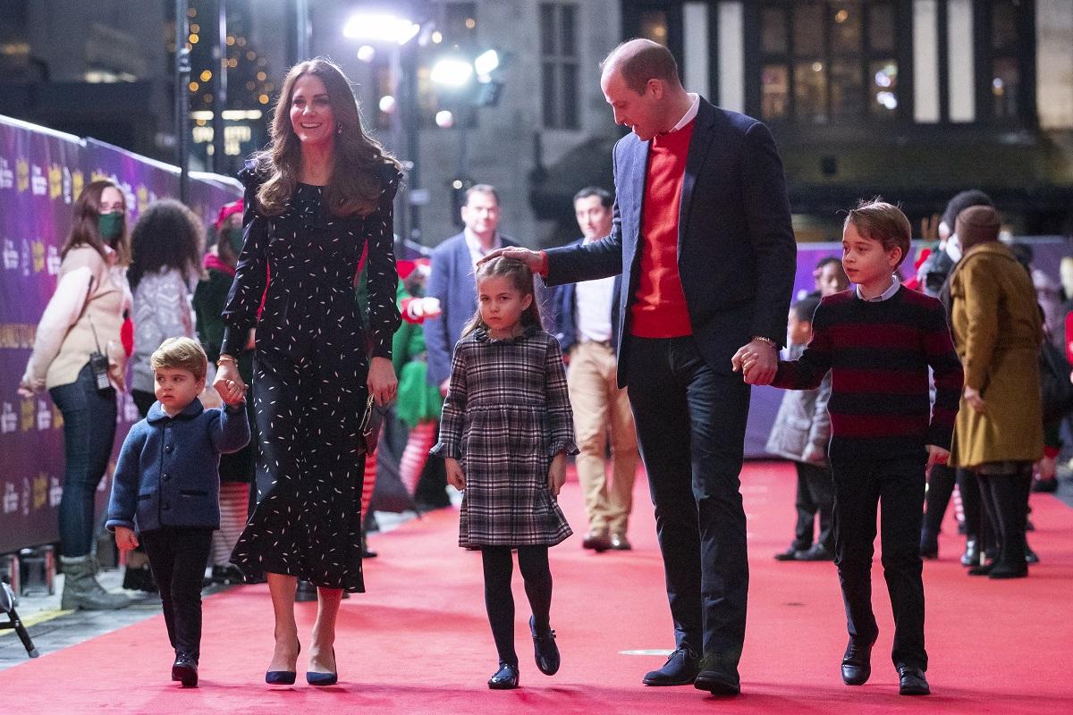 Kate Middleton într-o rochie elegantă neadră alături de Prințul William îmbrăcat la costum și o cămasă roșie, alături de cei trei copii pe covorul roșu care se îndreaptă către o excursie în care Kate Middleton a organizat o plimbare cu elicopterul pentru familia sa