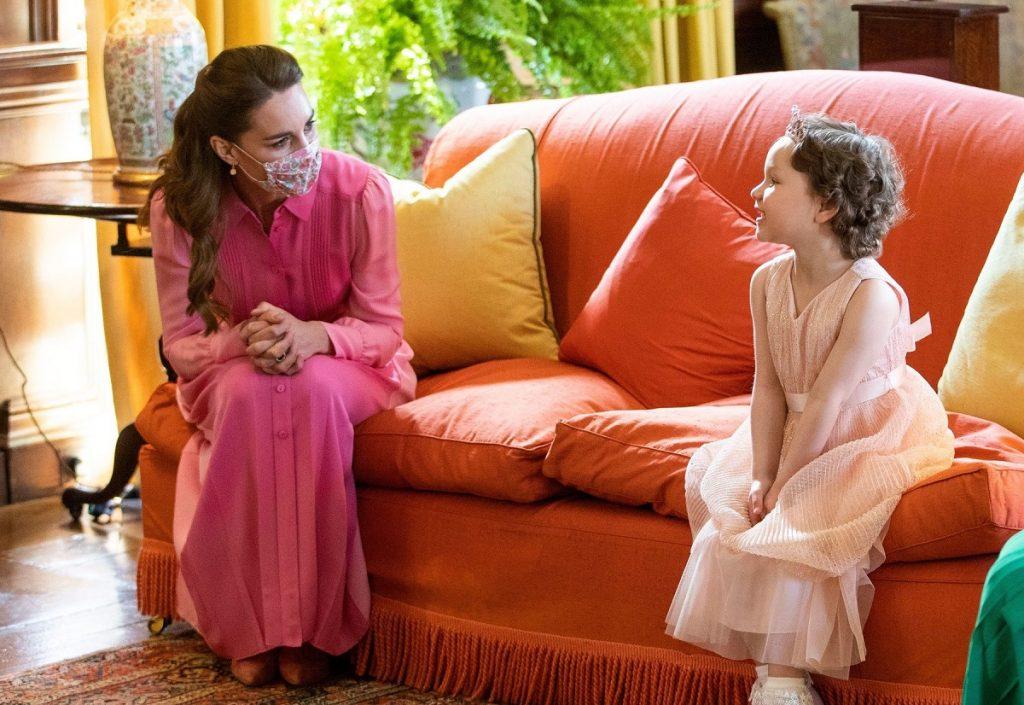 Kate Middleton într-o rochie lungă roz stând pe o canapea orange alături de micuța Mila Sneddon îmbrăcată la fel ca o prințesă