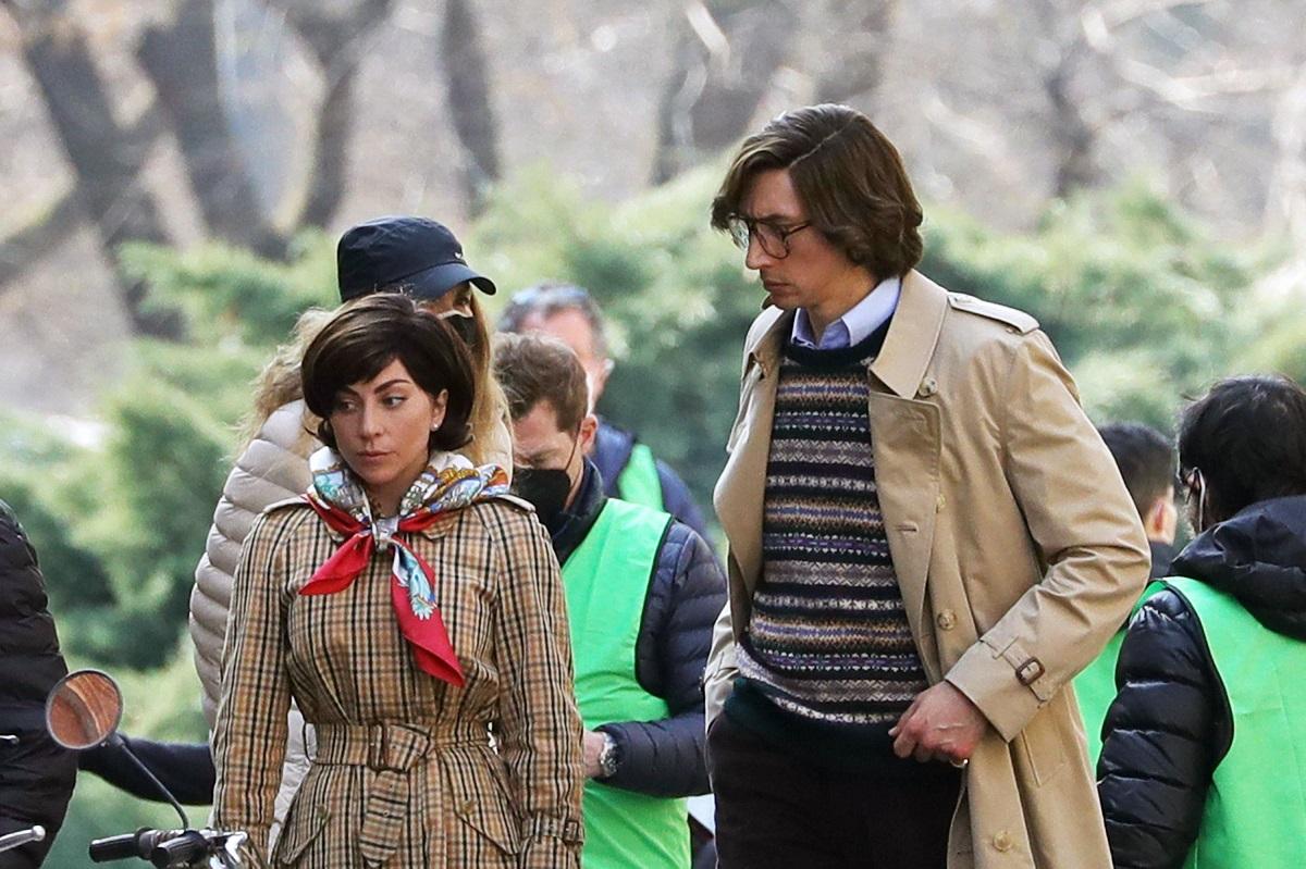 Lady Gaga îmbrăcată într-un palton crem cu carouri alături de actorul Adam Driver care poartă ochelari pe platourile de filmare cânt filmările pentru House of Gucci încă nu s-au încheiat