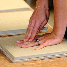 Mâinile Ducesei Kate Middleton așezate pe o plăcuță din ceramică pentru a face un mulaj al formei acestora