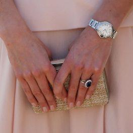 mâinile Ducesei Kate în timp ce ține o geantă în mână și este îmbrăcată cu o fustă roz pal