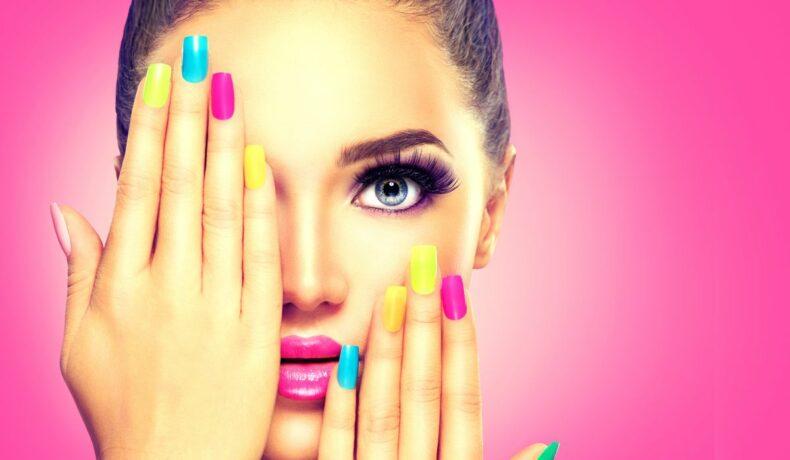 O fată, își acoperă o parte din față cu o manichiură colorată, pe un fundal roz