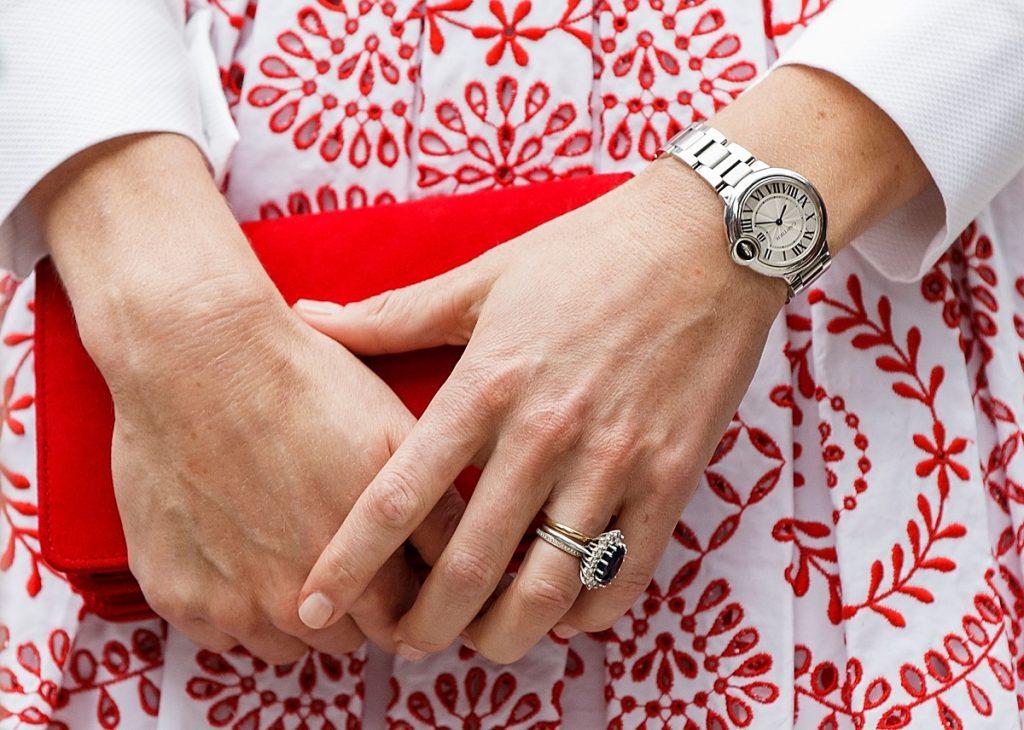 Mâinile Ducesei Kate în timp ce țin o geantă tip clutch pentru a evidenția care este manichiura preferată a Duceselor Kate Middleton și Meghan Markle