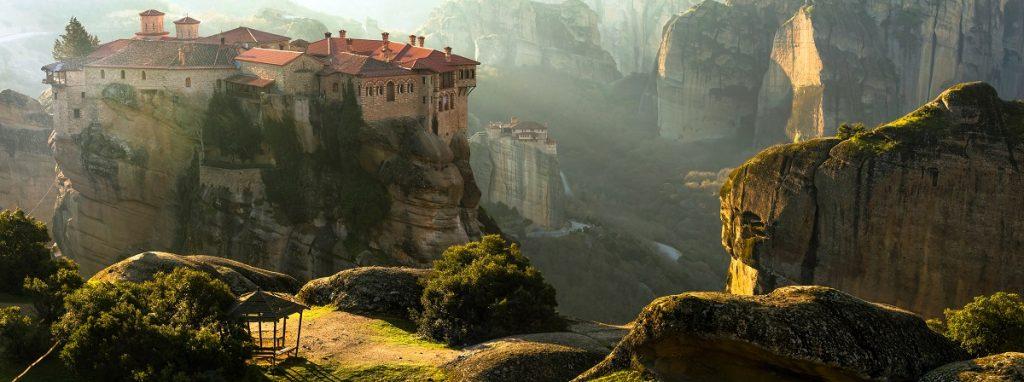 fotografie care surprinde orașul Meteora din Grecia cu stâncile acoperite de verdeață și casele localnicilor situate în vârf de creste