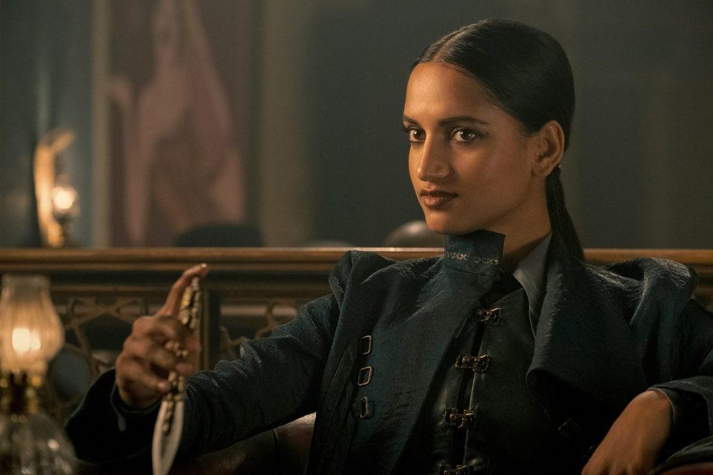 Actrița Amita Suman în rolul personajului Inej Ghafa din serialul Shadow and Bone îmbrăcată cu un sacou negru în timp ce privește la cameră într-una din scenele din serial
