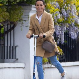 Pippa Middleton zâmbind în timp ce se plimbă cu trotineta și este îmbrăcată într-un palton crem, blugi și are o gentuță neagră